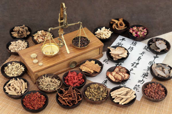 Chinese medicine ingredients with scales and calligraphy. Translation reads as chinese herbal medicine as increasing the body's ability to maintain body and spirit health and balance energy.