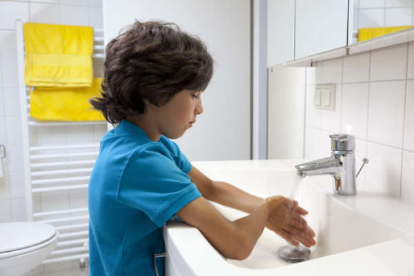 young boy washing hands in bathroom sink