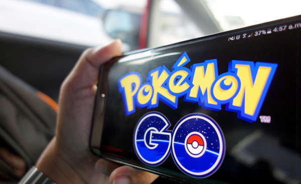 Person holding a handheld device with the Pokémon Go logo on the screen