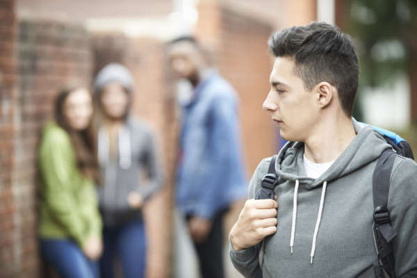 Student walking with a backpack and looking over his shoulder at a group of three other students hanging out