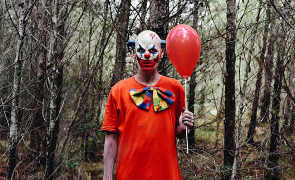 creepy-looking clown holding a balloon in a forest
