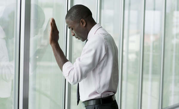 Black American leaning against window, looking dejected