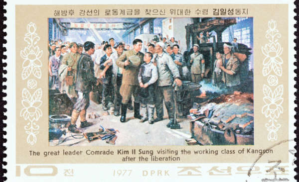 1977 postal stamp from North Korea depicting Kim Il Sung with workers