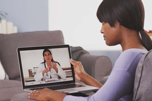 Woman looking at laptop computer, videoconferencing with a therapist