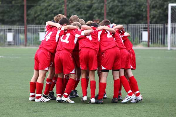 Schools boys in red soccer uniforms in a huddle