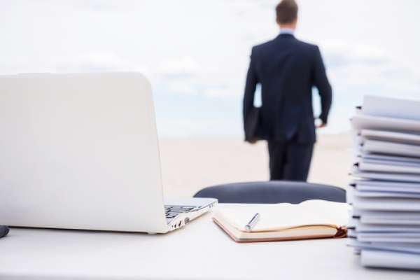 man in suit with briefcase and desk full of papers